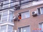 空调外机摇摇欲坠 消防队员紧急拆卸
